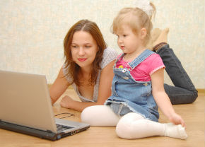 mom looking at laptop with child