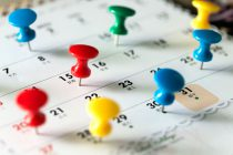 103360766 - various color thumb tack pins on calendar as reminder