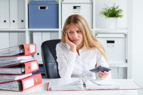 54644779 - pensive business woman calculates taxes at desk in office